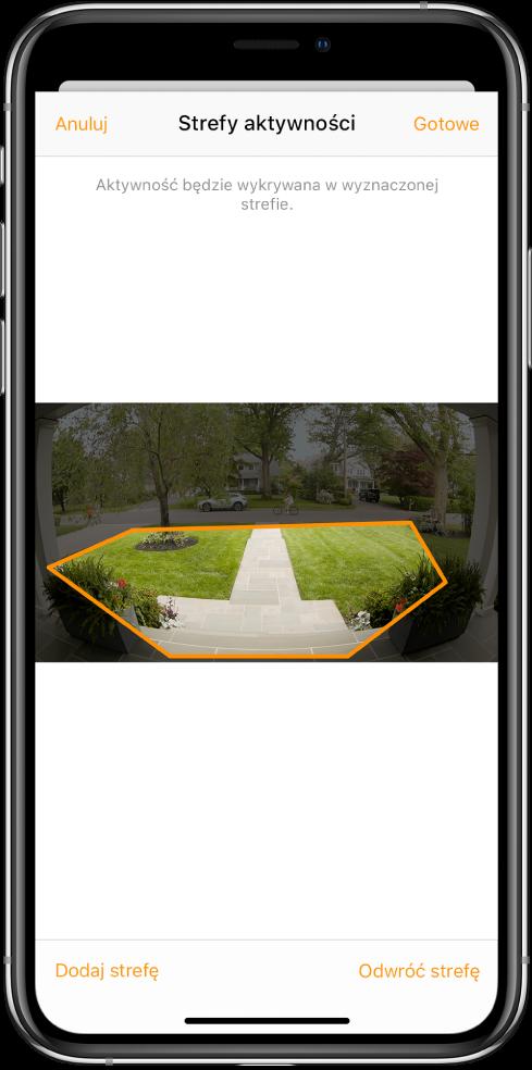 Ekran iPhone'a ze strefą aktywności na obrazie rejestrowanym przez wideodomofon. Strefa aktywności obejmuje ganek iwejście, ale nie obejmuje ulicy ipodjazdu. Nad obrazem widoczne są przyciski Anuluj iGotowe. Poniżej znajdują się przyciski Dodaj strefę oraz Odwróć strefę.