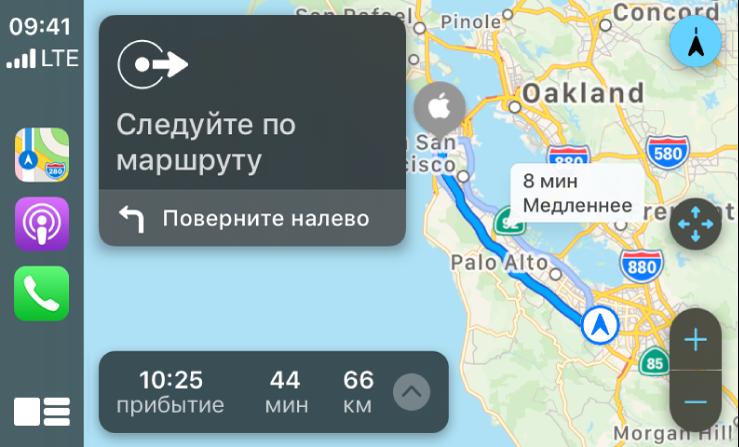 CarPlay. Слева показаны значки приложений «Карты», «Подкасты» и«Телефон», в центре— карта савтомобильным маршрутом сэлементами управления масштабом, подробными инструкциями понавигации ипримерным временем прибытия.
