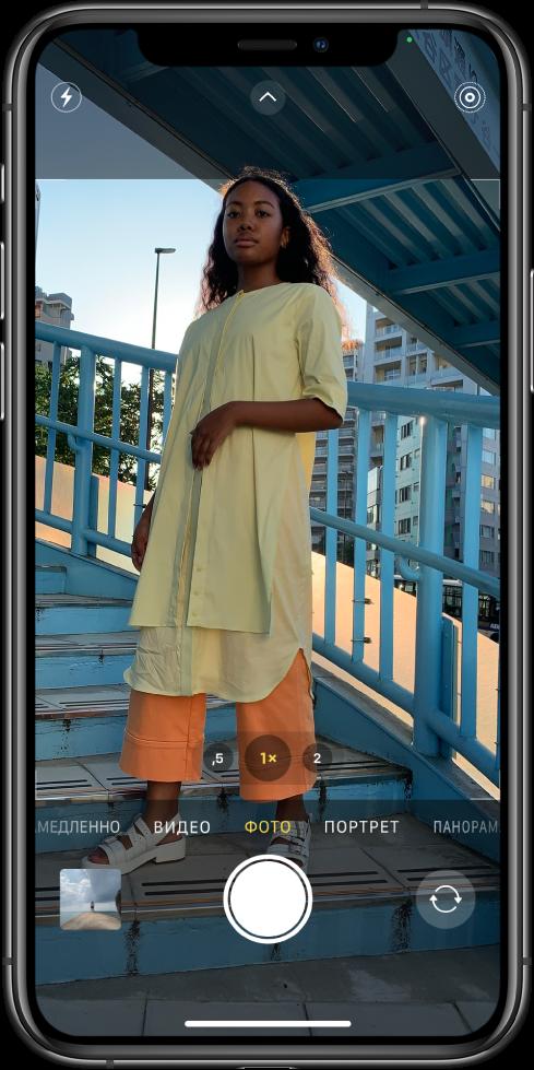 Камера в режиме съемки фото; другие режимы отображаются слева и справа под видоискателем. Кнопки вспышки, элементов управления камерой иLivePhoto отображаются в верхней части экрана. Кнопка просмотра снятых фото ивидео находится в левом нижнем углу. Кнопка съемки фото расположена по центру в нижней части экрана, а кнопка выбора камеры назадней панели— в правом нижнем углу.