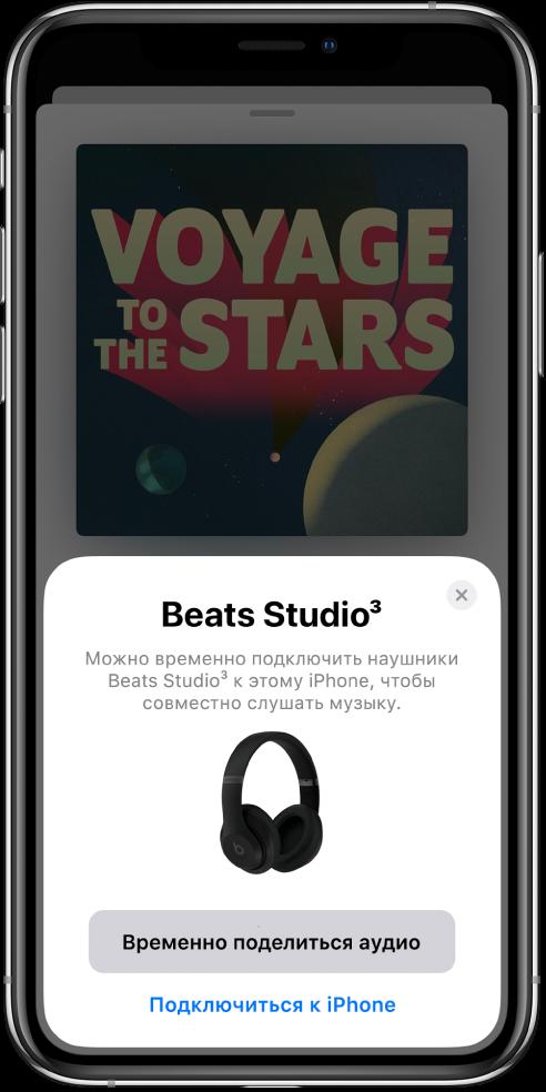 На экране iPhone показаны наушники Beats. У нижнего края экрана— кнопка «Временно поделиться аудио».