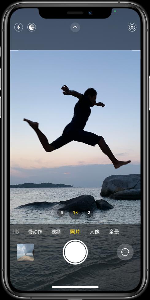 """""""照片""""模式的相机屏幕,其他模式位于取景器下方的左右两侧。屏幕顶部是""""闪光灯""""、""""夜间""""模式、""""相机控制""""和""""实况照片""""的按钮。相机模式下方从左到右依次是""""照片与视频显示器""""按钮、""""拍照""""按钮和""""相机选取器后置""""按钮。"""