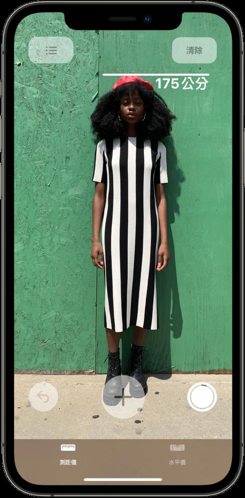 已測量人物的身高,測量的高度在人物的頭頂顯示。右側邊緣的「拍照」按鈕正用來拍攝測量的照片。綠色的「相機使用中」指示器顯示於右上角。