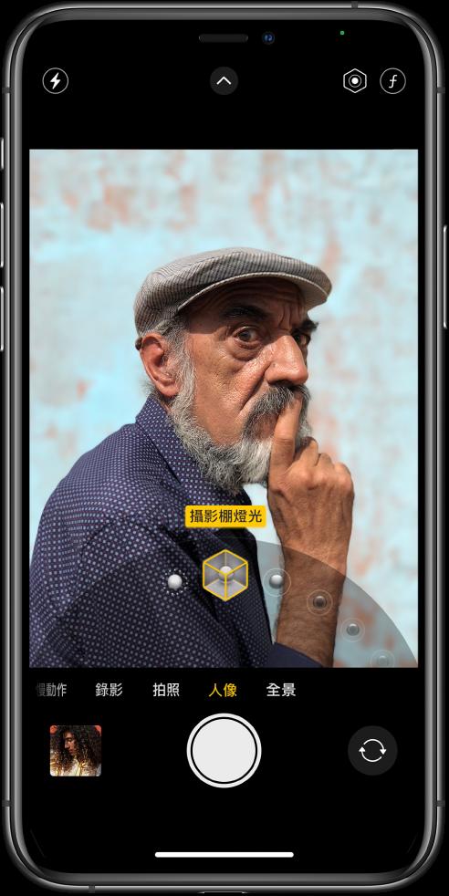 「人像」模式下的「相機」畫面;在取景窗中的主體清晰而背景模糊。用於選取「人像」光線效果的轉盤在景觀窗底部打開,並選取了「攝影棚燈光」。螢幕左上角為「閃光燈」按鈕、最上方中央為「相機控制項目」按鈕,右上角則為用於調整「人像」光線強度和景深控制的按鈕。螢幕底部由左至右為「照片和影片檢視器」按鈕、「拍照」按鈕和「相機選擇器後置」按鈕。