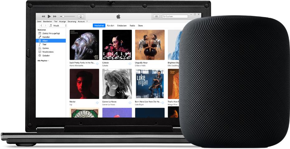 Ein PC mit iTunes auf dem Bildschirm und einem HomePod in der Nähe