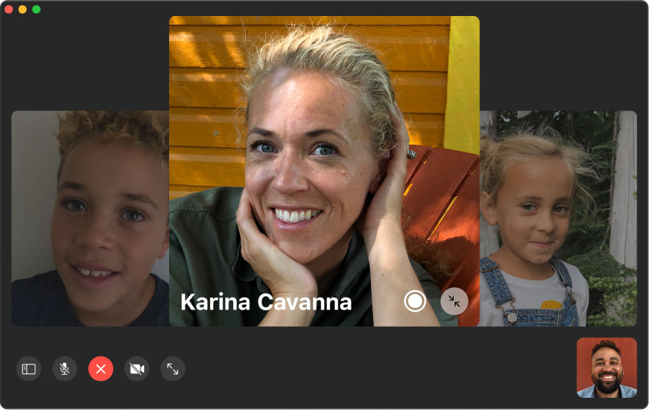 The FaceTime window showing a group call. The person who initiated the call is shown in a tile in the bottom-right corner. A large tile in the middle of the window shows a participant, along with a Live Photo button in the middle of the tile that callers can click to capture the moment.