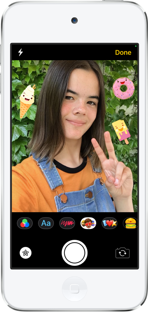 The Messages effects screen. The top of the screen shows the front camera frame. iMessage stickers are around the subject in the frame. Below the frame, from left to right, are the filters, text, shapes, Memoji, Emoji, and iMessage app buttons. At the bottom of the screen, from left to right, are the Effects, Shutter, and Camera Chooser Back Facing buttons.