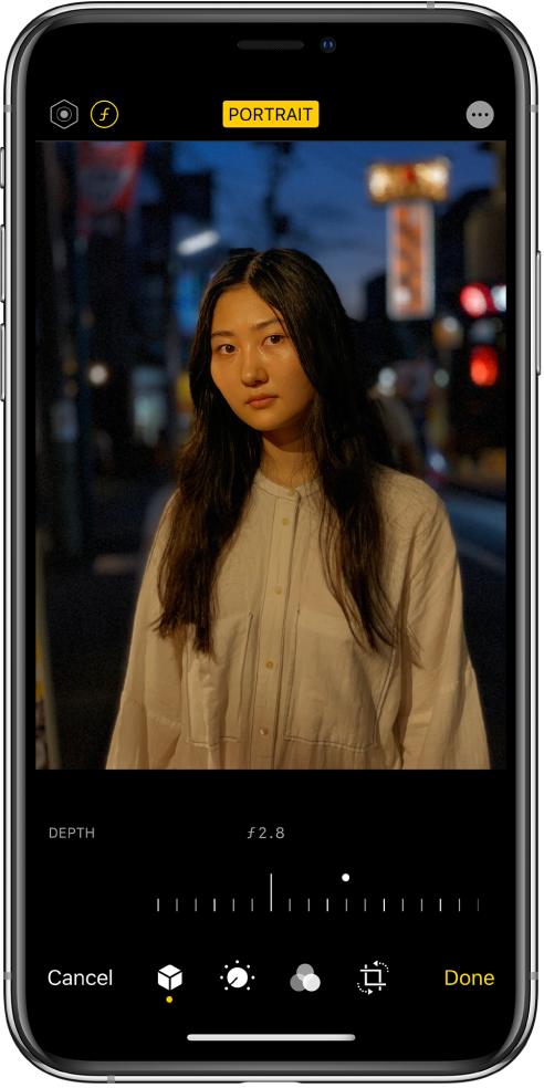 Екранът Edit (Редактиране) на снимка в режим Portrait (Портрет) Горе вляво на екрана са бутоните Lighting Intensity (Интензивност на осветлението) и Depth Adjustment (Настройване на дълбочина на рязкост). Горе в средата на екрана е бутонът Portrait (Портрет), горе вдясно е бутонът Plug-ins (Допълнения). Снимката е в центъра на екрана, а под снимката е плъзгачът за регулиране на Depth Adjustment (Настройване на дълбочина на рязкост). Под плъзгача, от ляво надясно са бутоните Cancel (Откажи), Portrait (Портрет), Adjust (Настройка), Filters (Филтри), Crop (Изрязване) и Done (Готово).
