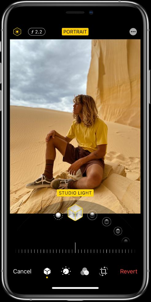 Екранът Edit (Редактиране) на снимка в режим Portrait (Портрет) Горе вляво на екрана са бутоните Lighting Intensity (Интензивност на осветлението) и Depth Adjustment (Настройване на дълбочина на рязкост). Горе в средата на екрана е бутонът Portrait (Портрет), горе вдясно е бутонът Plug-ins (Допълнения). Снимката е в центъра на екрана, под снимката е плъзгачът за избор на ефект Portrait Lighting (Портретно осветление), а под нея има плъзгач за настройване на стойността. В долната част на екрана, от ляво надясно са бутоните Cancel (Откажи), Portrait (Портрет), Adjust (Настройка), Filters (Филтри), Crop (Изрязване) и Revert (Отмени).
