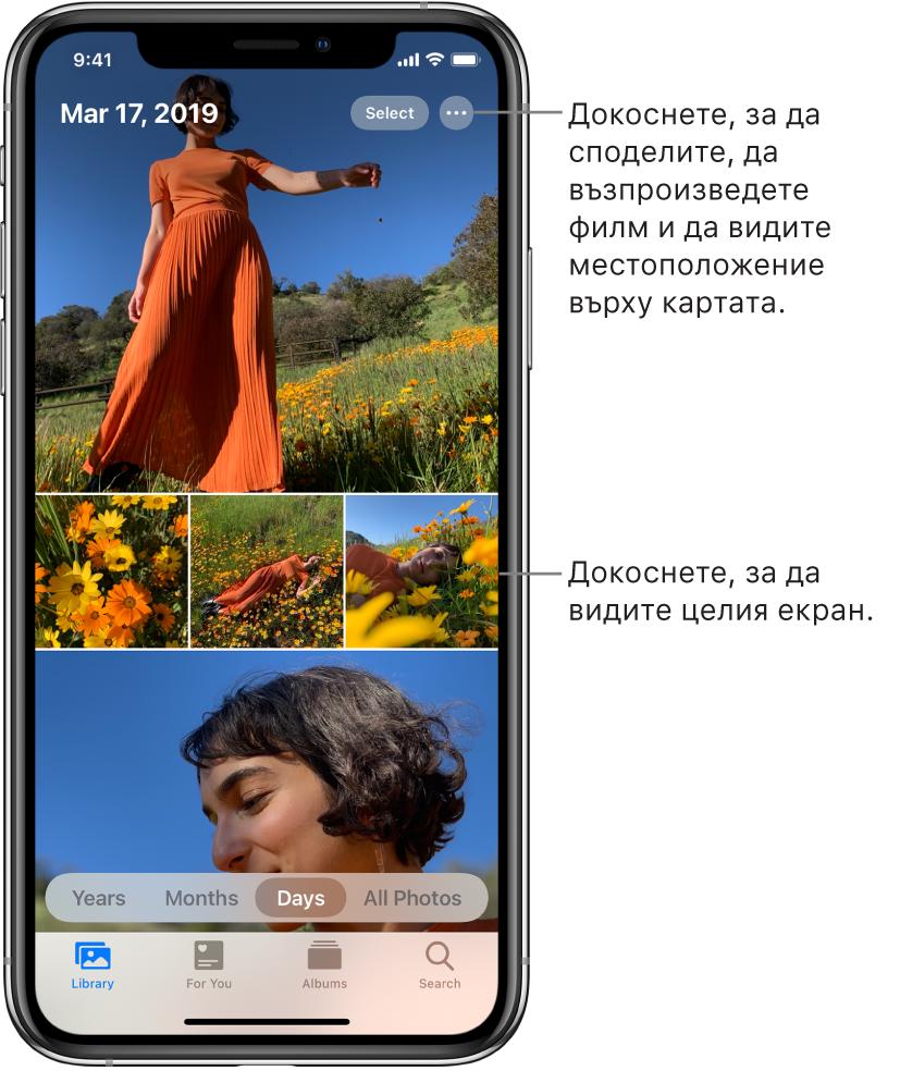Библиотеката снимки, показана в изглед Days (Дни). Екранът е запълнен с умалени изображения на снимки. Горе вляво на екрана са датата и мястото, където са били направени снимките. Горе вдясно са бутоните Select (Избор) и More Options (Повече опции) за споделяне на снимките и показване на подробна информация. Под умалените изображения са опциите са преглед на фото библиотеката по Years (Години), Months (Месеци), Days (Дни) и All Photos (Всички снимки). В долния край са етикетите Library (Библиотека), For You (За теб), Albums (Албуми) и Search (Търсене).