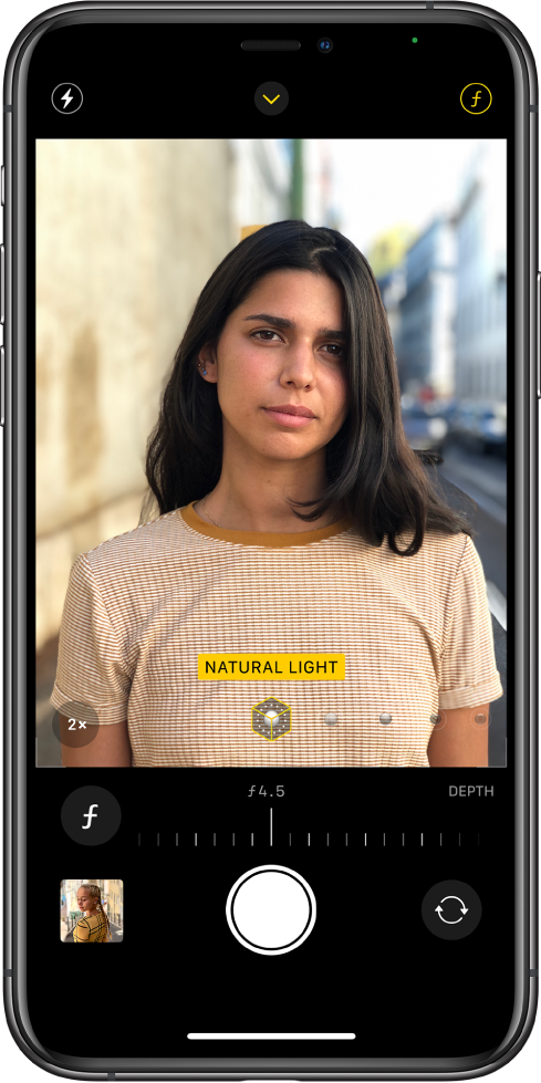 The Camera screen in Portrait mode. The Depth Adjustment button in the top-right corner of the screen is selected. In the view finder, a box shows that the Portrait Lighting option is set to Natural Light, and there's a slider to change the lighting option. Below the view finder, there is a slider to adjust the Depth Control.
