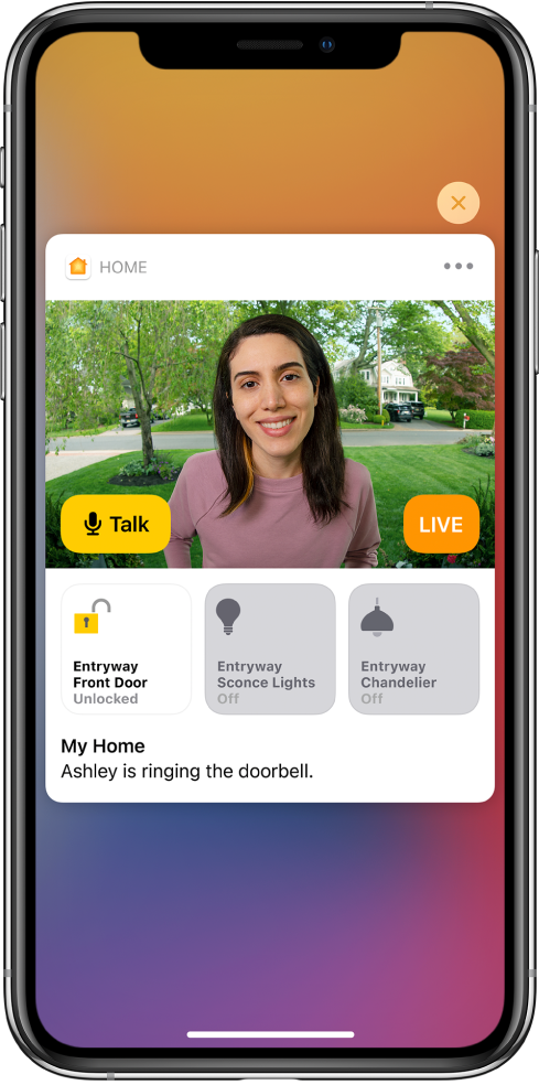 "A notification from Home on the iPhone screen. It shows a picture of a person at the front door with a Talk button at the left. Below are accessory buttons for the front door and entryway lights. The words ""Ashley is ringing the doorbell"" appear under the accessory buttons. A Close button is at the top right of the notification."