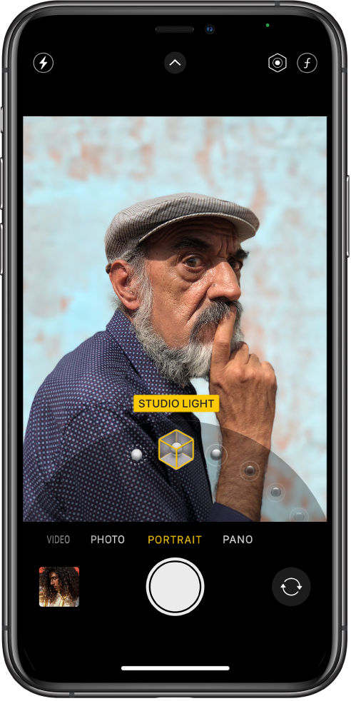 Rakenduse Camera-kuva režiimis Portrait; võtteobjekt on pildinäidikus terav ning taust hägustatud. Kaadri allservas on avatud ketas Portrait-valgustusefektide valimiseks ning valitud on Studio Light. Ekraani ülemises vasakus servas on nupp Flash, üleval keskel on nupp Camera Controls ning üleval paremal on nupud Portrait-valgustusefekti intensiivsuse ning teravussügavuse reguleerimiseks. Ekraani allservas on (vasakult paremale) nupp Photo and Video Viewer, nupp Take ning nupp Camera Chooser Back-Facing.
