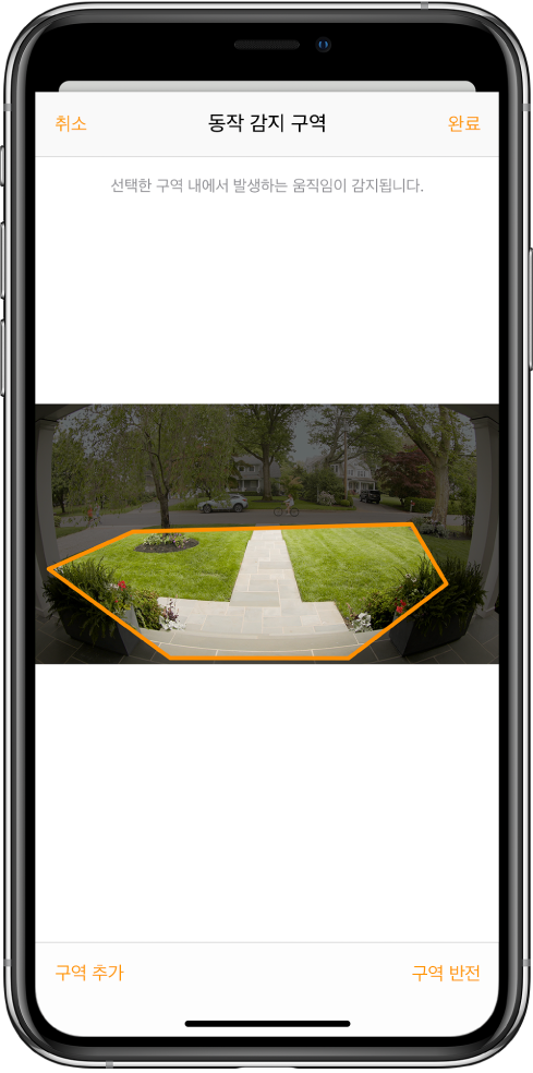 초인종 카메라로 촬영한 이미지 내 동작 감지 구역을 보여주는 iPhone 화면. 동작 감지 구역에는 현관과 보도가 포함되나 거리와 진입로는 제외됨. 이미지 위에 취소 및 완료 버튼이 있음. 아래에 구역 추가 및 구역 반전 버튼이 있음.