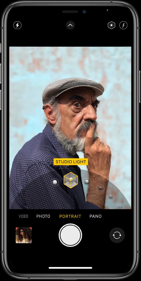 """Portreto režimu veikiančios programos """"Camera"""" ekranas; vaizdo ieškiklyje objektas ryškus, o fonas sulietas. Kadro apačioje atidarytas portreto apšvietimų efekto parinkiklis ir nustatyta studijinio apšvietimo parinktis. Ekrano viršutiniame kairiajame kampe yra blykstės mygtukas, viršuje centre yra fotoaparato valdiklių mygtukas, viršutiniame dešiniajame kampe– portreto apšvietimo intensyvumo koregavimo mygtukas ir gylio valdiklis. Ekrano apačioje, nuo kairės į dešinę, yra šie mygtukai: nuotraukų ir video peržiūros mygtukas, fotografavimo mygtukas ir fotoaparato pasirinkimo nukreipimo atgal mygtukas."""
