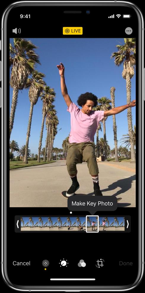"""Ekranas """"Live Photo"""", kurio ekrane pateikta nuotrauka """"Live Photo"""". Mygtukas """"Live"""" pateikiamas viršuje centre, o mygtukas """"Sound""""– viršuje kairėje. Po """"Live Photo"""" yra kadro peržiūra su aktyviu """"Make Key Photo"""" mygtuku. Abiejuose kadrų žiūryklės galuose pateikiamos dvi juostos, kurias naudojant galima apkarpyti """"Live Photo""""."""