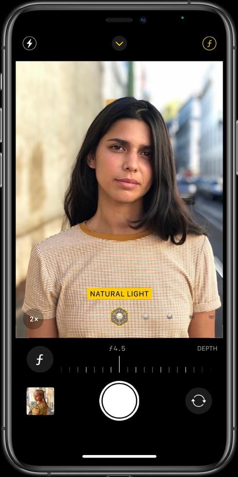 """Fotoaparato ekranas režimu """"Portrait"""". Pasirinktas """"Depth Adjustment"""" mygtukas viršutiniame dešiniajame ekrano kampe. Kameros vaizdo ieškiklyje rodoma, kad """"Portrait Lighting"""" apšvietimo parinktis nustatyta kaip """"Natural Light"""" apšvietimas, o apšvietimą galite pakeisti slankikliu. Žemiau kameros vaizdo ieškiklio yra """"Depth Control"""" reguliavimo slankiklis."""