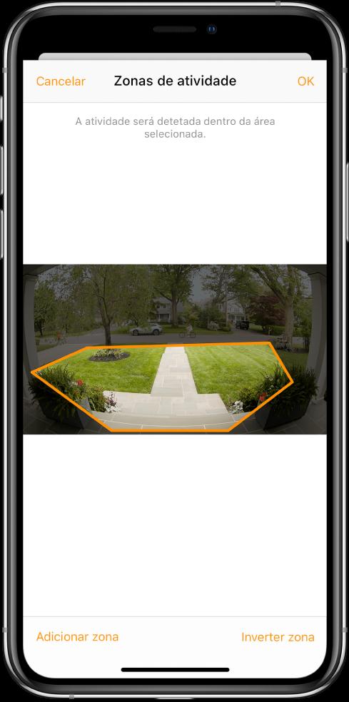 """O ecrã do iPhone a mostrar uma zona de atividade dentro de uma imagem captada por uma câmara de campainha. A zona de atividade abrange o alpendre e a entrada, mas exclui o passeio e a estrada. Os botão Cancelar e OK encontrm-se por cima da imagem. Os botões """"Adicionar zona"""" e """"Inverter zona"""" encontram-se por baixo."""