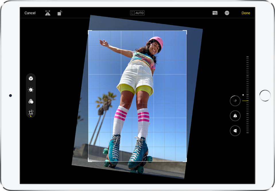 iPad in landscape orientation. In the center of the screen is a photo in Edit mode with an overlay grid and a crop frame. On the left side of the screen, the Crop button is selected. On the right side of the screen are the geometry enhancement options. Straighten is selected and the intensity slider is adjusted to -5.