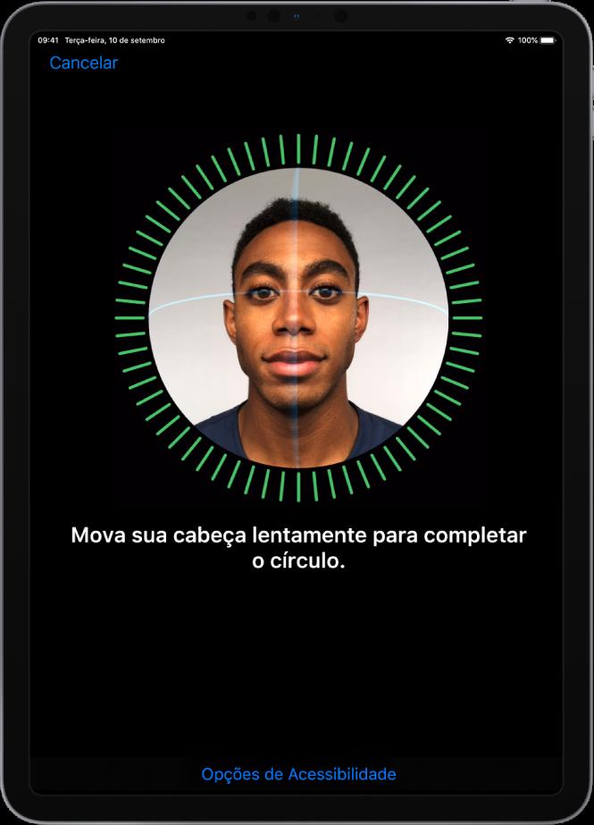 Tela de configuração do reconhecimento do Face ID. Um rosto é mostrado na tela, envolto por um círculo. Abaixo disso, um texto instrui a mover a cabeça lentamente para completar o círculo.