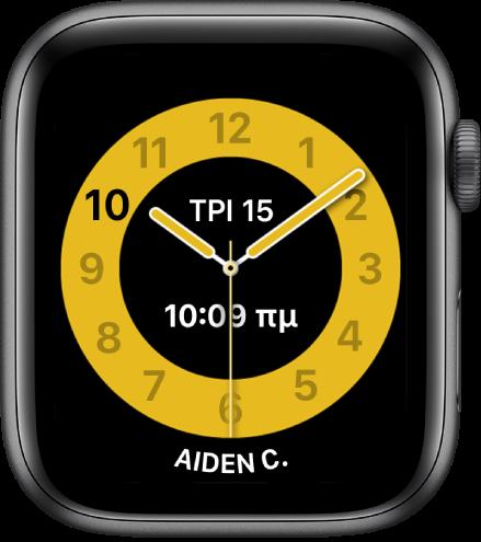 Η πρόσοψη ρολογιού «Ώρα σχολείου» όπου φαίνεται ένα αναλογικό ρολόι με την ημερομηνία και την ψηφιακή ώρα κοντά στο πάνω μέρος και την ώρα παρακάτω. Το όνομα του ατόμου που χρησιμοποιεί το ρολόι εμφανίζεται στο κάτω μέρος.