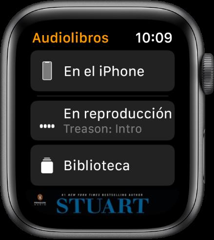 """AppleWatch con la pantalla Audiolibros, en la que se ve el botón """"En el iPhone"""" arriba, los botones """"Ahora suena"""" y Biblioteca debajo, y parte de la portada de un audiolibro en la parte inferior."""