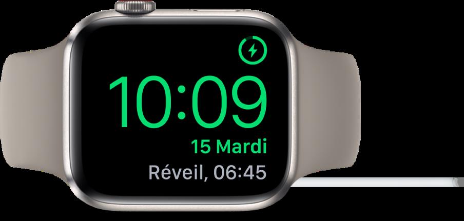 AppleWatch placée sur sa tranche et connectée au chargeur. L'écran montre le symbole de recharge dans le coin supérieur droit, l'heure actuelle en dessous et l'heure du prochain réveil.