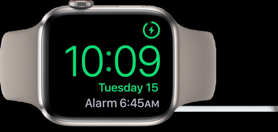 """Ant šono padėtas ir prie įkroviklio prijungtas """"AppleWatch"""", kurio ekrano viršutiniame dešiniajame kampe rodomas įkrovimo simbolis, o po juo pateikiami esamas laikas ir kito žadintuvo laikas."""