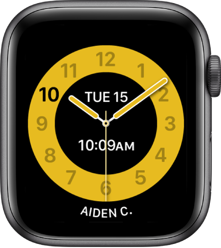 Ciparnīva Schooltime, kuras augšdaļā redzams analogais pulkstenis ar datumu un laiku zem tā. Apakšā ir tās personas vārds, kura izmanto pulksteni.