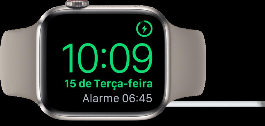 AppleWatch posicionado de lado e conectado ao carregador, com a tela mostrando o símbolo de carregamento no canto superior direito, a hora atual abaixo e o horário do próximo alarme.