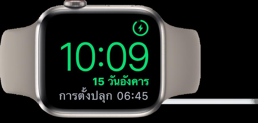 Apple Watch ที่วางตะแคง และเชื่อมต่ออยู่กับที่ชาร์จ โดยหน้าจอแสดงสัญลักษณ์การชาร์จตรงมุมขวาบนสุด เวลาปัจจุบันอยู่ด้านล่างสัญลักษณ์การชาร์จ และเวลาของการตั้งปลุกครั้งต่อไป