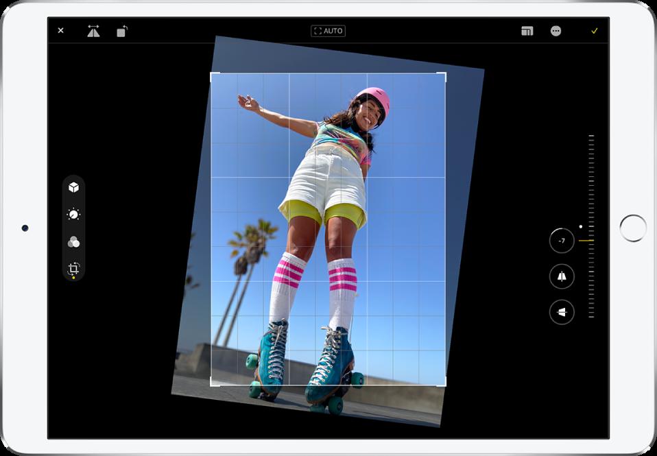 """iPad im Querformat. In der Mitte des Bildschirms befindet sich ein Foto im Modus """"Bearbeiten"""" mit einem Raster und einem Beschnittrahmen. Auf der linken Seite des Bildschirms ist die Taste """"Beschneiden"""" ausgewählt. Auf der rechten Seite des Bildschirms befinden sich Optionen zur geometrischen Optimierung. Die Taste """"Begradigen"""" ist ausgewählt und der Regler für die Intensität ist auf -5 eingestellt."""