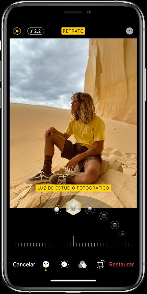 """La pantalla Editar de una foto tomada en el modo Retrato. En la parte superior izquierda de la pantalla se encuentran los botones """"Intensidad de iluminación"""" y """"Ajuste de profundidad"""". En la parte superior central de la pantalla se encuentra el botón Retrato y, en la parte superior derecha, está el botón Módulos. La foto se encuentra en el centro de la pantalla y debajo de la foto hay un regulador para seleccionar el efecto de luz de retrato y, debajo de este, un regulador para ajustar el valor. En la parte inferior de la pantalla, de izquierda a derecha, se encuentran los botones Cancelar, Retrato, Ajustar, Filtros, Recortar y Restaurar."""