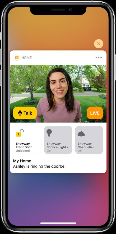"""""""Home"""" pranešimas rodomas """"iPhone"""" ekrane. Jame rodoma prie durų esančio asmens nuotrauka ir kairėje pateikiamas mygtukas """"Talk"""". Žemiau yra įėjimo durų ir tako apšvietimo priedų mygtukai. Žodžiai """"Ashley skambina durų skambučiu"""" atsiranda po papildomais mygtukais. Pranešimo viršuje, dešinėje yra uždarymo mygtukas."""