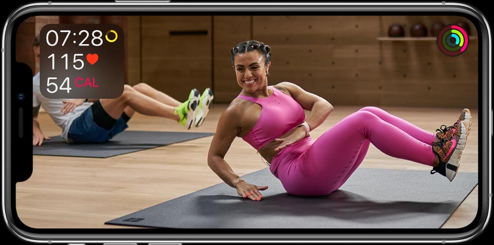 En skjerm som viser en trener som leder en treningsøkt i Apple Fitness Pluss. Informasjon om treningstid, puls og forbrente kalorier vises øverst til venstre. Ringene for bevegelse, trening og oppreist vises øverst til høyre.