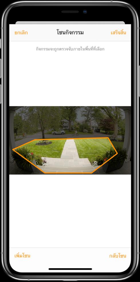 หน้าจอ iPhone ที่แสดงโซนกิจกรรมภายในภาพที่ถ่ายโดยกล้องกริ่งประตู โซนกิจกรรมประกอบด้วยระเบียงด้านหน้าและทางเดิน แต่ไม่รวมถนนและทางรถ ปุ่มยกเลิกและเสร็จสิ้นอยู่เหนือภาพ ปุ่มเพิ่มโซนและสลับโซนอยู่ด้านล่าง