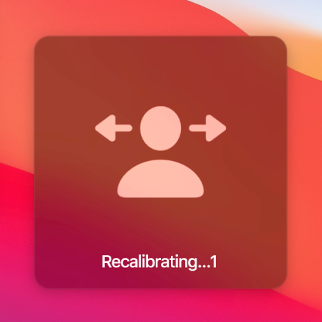 """The on-screen countdown for head pointer recalibration, showing """"Recalibrating…1."""""""