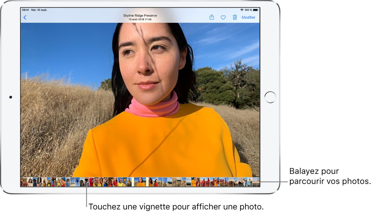 Une photo en plein écran, avec les vignettes d'autres photos de la photothèque au bas de l'écran. En haut à gauche se trouve le bouton Retour permettant de parcourir à nouveau les photos. En haut à droite, vous trouverez les boutons Partager, Aimer, Supprimer et Modifier.