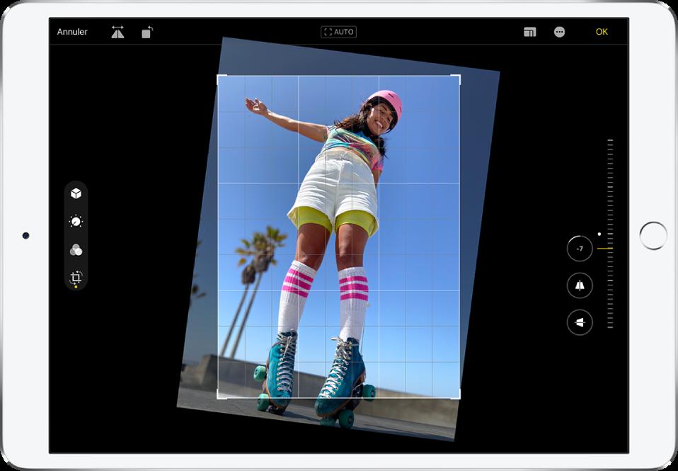 L'iPad en orientation paysage. Au centre de l'écran se trouve une photo en mode édition avec une grille en superposition et un cadre pour recadrer l'image. Sur le côté gauche de l'écran, le bouton Recadrer est sélectionné. Sur le côté droit de l'écran se trouvent les options d'amélioration de la géométrie. L'option Redresser est sélectionnée et le curseur d'intensité est réglé à -5.
