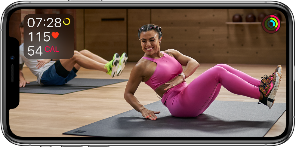 A screen showing a trainer leading an Apple Fitness Plus workout. Information about workout time, heart rate, and calories burned appears in the top left. Progress rings for move, exercise, and stand goals appear at the top right.