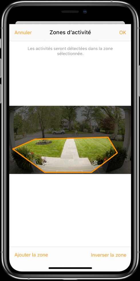 Écran d'iPhone montrant une zone d'activité dans une image prise par une caméra de porte. La zone d'activité inclut un perron et une allée, mais exclut la rue et la voie d'accès. Les boutons Annuler et OK se trouvent au-dessus de l'image. Les boutons «Ajouter la zone» et «Inverser la zone» se trouvent en dessous.