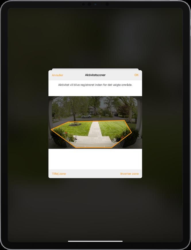 Skærm på iPad, der viser en aktivitetszone med et billede taget af et dørklokkekamera. Aktivitetszonen omfatter terrassen og gangstien foran huset, men ikke gaden og indkørslen. Over billedet findes knapperne Annuller og OK. Knapperne Tilføj zone og Inverter zone er vist nedenfor.