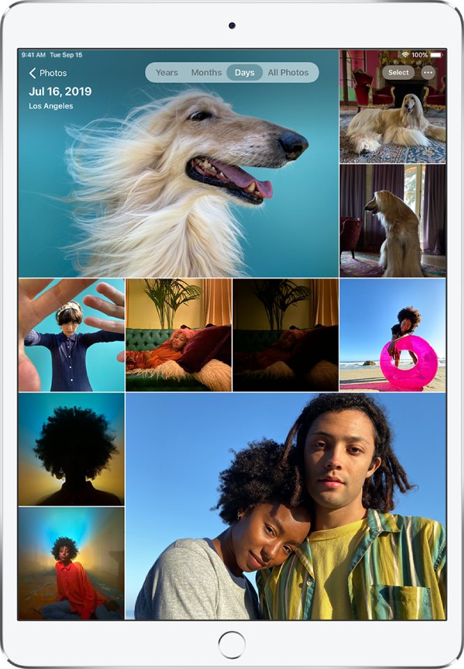 The photo library displayed in Days view. A selection of photo thumbnails fills the screen. In the top left of the screen is the Photos button to open the sidebar. Below the Photos button is the date and location where the photos displayed on the screen were taken. In the top center are options to browse photos by Years, Months, Days, or All Photos; Days is selected. In the top right of the screen are the Select and More Options buttons.