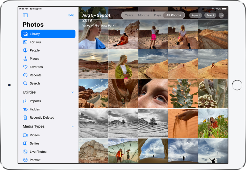On the left side of a screen in Photos is a sidebar to select Library, For You, People, Places, and other categories; Library is selected.. The rest of the screen shows the photo library in All Photos view. At the top of the photo library is the date and location where the photos were taken. In the top center are options to view photos by Years, Months, Days, and All Photos; All Photos is selected. In the top right of the screen are the Aspect, Select, and More buttons.