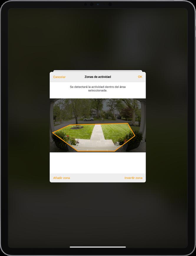 """Pantalla del iPad con una zona de actividad en una imagen tomada por la cámara de un timbre. La zona de actividad incluye el porche y el acceso a la casa, pero excluye la calle y la entrada al garaje. Sobre la imagen están los botones Cancelar y OK. Debajo están los botones """"Añadir zona"""" e """"Invertir zona""""."""
