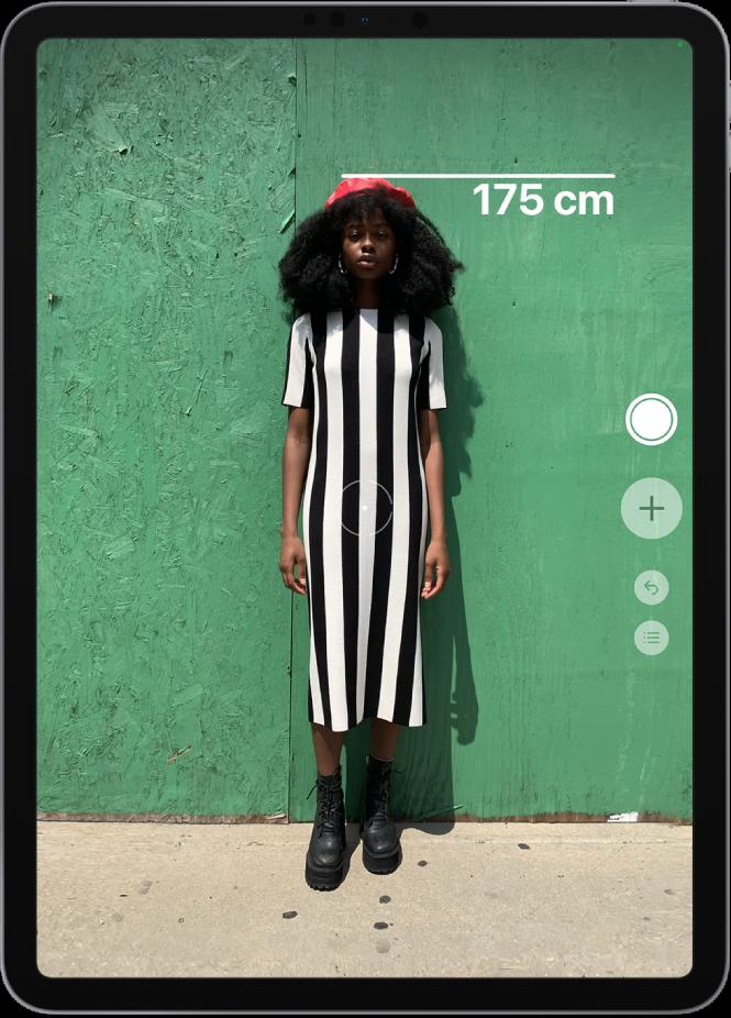 """L'altezza di una persona viene misurata, sulla testa della persona viene mostrata una misurazione. Il pulsante per scattare le foto è attivo nella parte destra dello schermo, da lì è possibile scattare una foto della misurazione. L'indicatore verde """"Fotocamera in uso"""" viene visualizzato in alto a destra."""