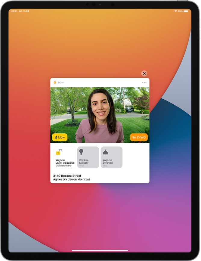 """Powiadomienie zaplikacji Dom na ekranie iPada. Zawiera ono zdjęcie osoby stojącej za drzwiami wejściowymi. Po lewej widoczny jest przycisk Mów. Poniżej znajdują się przyciski akcesoriów: drzwi wejściowych oraz świateł. Poniżej przycisków akcesoriów widoczny jest adres domu oraz napis """"Agnieszka dzwoni do drzwi"""". Wprawym górnym rogu powiadomienia znajduje się przycisk Zamknij."""