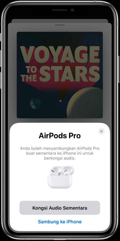 Skrin iPhone menunjukkan AirPods dalam bekas pengecas yang terbuka. Berdekatan bahagian bawah skrin ialah butang untuk berkongsi audio secara sementara.