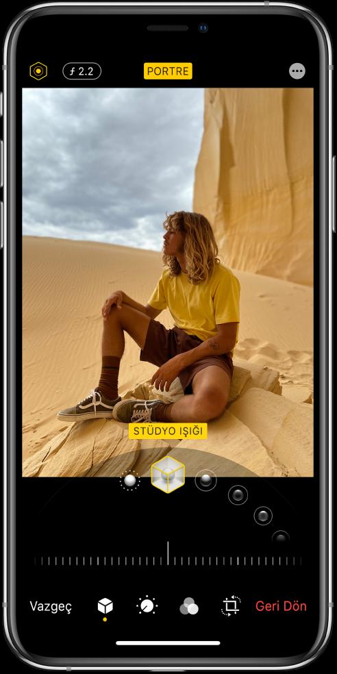 Portre modu fotoğrafının Düzenle ekranı. Ekranın sol üstünde Işık Yoğunluğu düğmesi ve Derinlik Ayarı düğmesi bulunuyor. Ekranın üst ortasında Portre düğmesi açık ve sağ üstte Yazılım Ekleri düğmesi var. Fotoğraf ekranın ortasında ve fotoğrafın altında Portre Işık Efektini seçmek için bir sürgü bulunuyor ve onun da altında değeri ayarlayan bir sürgü var. Ekranın altında soldan sağa doğru Vazgeç, Portre, Ayarla, Filtreler, Kırp ve Geri Dön düğmeleri bulunuyor.