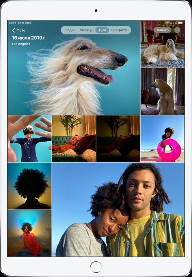 В медиатеке открыт режим просмотра «Дни». На экране отображается подборка миниатюр фотографий. Влевом верхнем углу экрана находится кнопка «Фото» для открытия бокового меню. Над кнопкой «Фото» показаны дата иместо съемки фотографии, которая отображается наэкране. Наверху вцентре находятся элементы управления для выбора режима просмотра «Годы», «Месяцы», «Дни» или «Все фото». Выбран вариант «Дни». Вправом верхнем углу экрана находятся кнопка «Выбрать» икнопка «Еще».