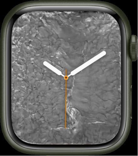 중앙에 아날로그 시계가 있고 주위에 리퀴드 메탈이 있는 리퀴드 메탈 시계 페이스.